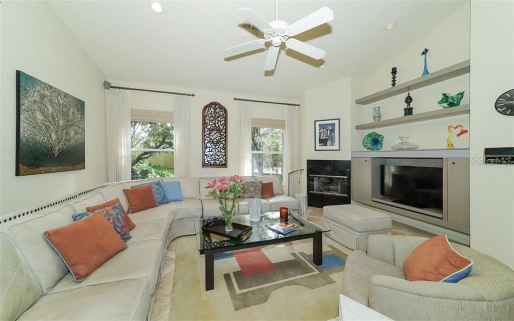 Family room with built in shelving, recessed lighting, ceiling fan & gas fireplace, open to the kitchen. - Single Family Home for sale at 6125 Varedo Ct, Sarasota, FL 34243 - MLS Number is A4420656