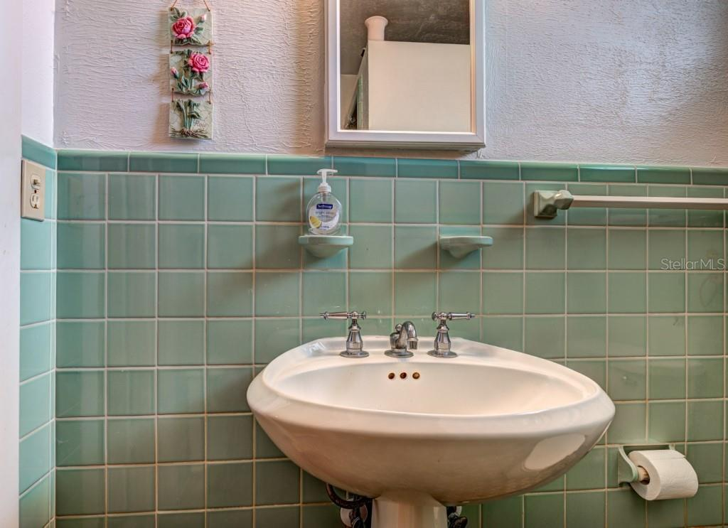 Bathroom three has a pedestal sink and walk-in shower and is located just outside the third bedroom. - Single Family Home for sale at 1509 Flower Dr, Sarasota, FL 34239 - MLS Number is A4421898