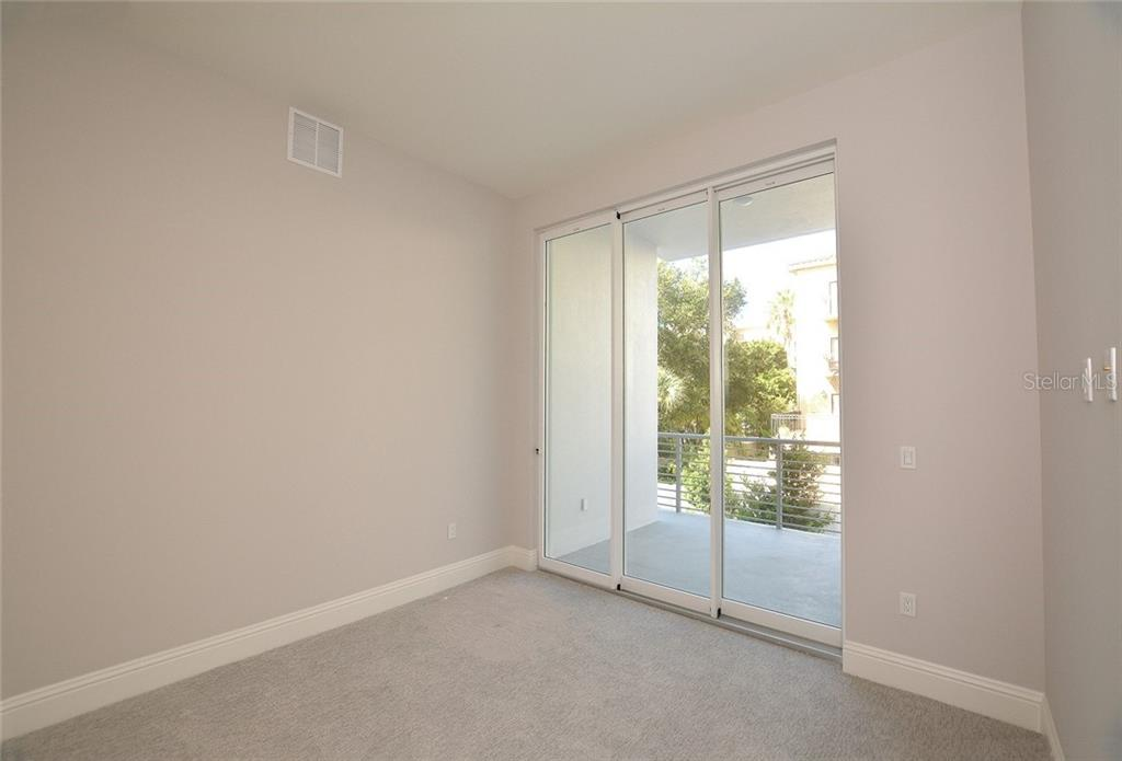 Bedroom 3 with terrace and private ensuite bath. - Condo for sale at 609 Golden Gate Pt #201, Sarasota, FL 34236 - MLS Number is A4422340