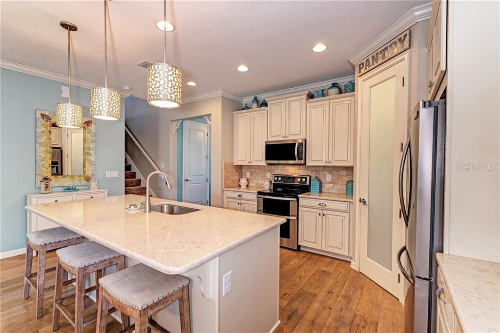 The kitchen island is over-sized with a large breakfast bar! - Single Family Home for sale at 5260 Bentgrass Way, Bradenton, FL 34211 - MLS Number is A4424484