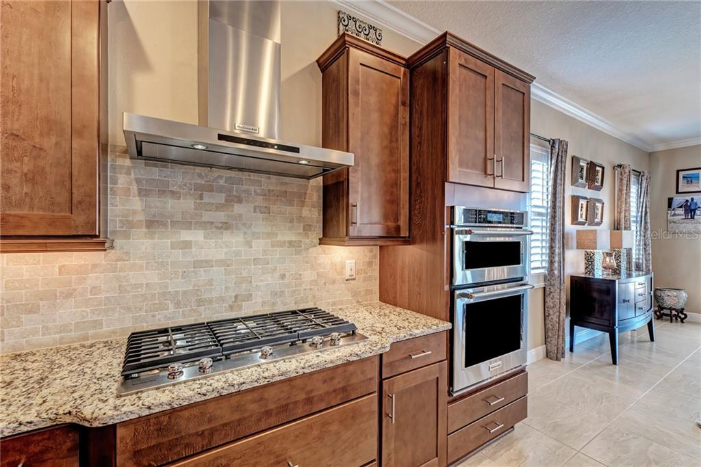 Kitchen with five burner gas range and double oven - Single Family Home for sale at 5712 Tidewater Preserve Blvd, Bradenton, FL 34208 - MLS Number is A4424693