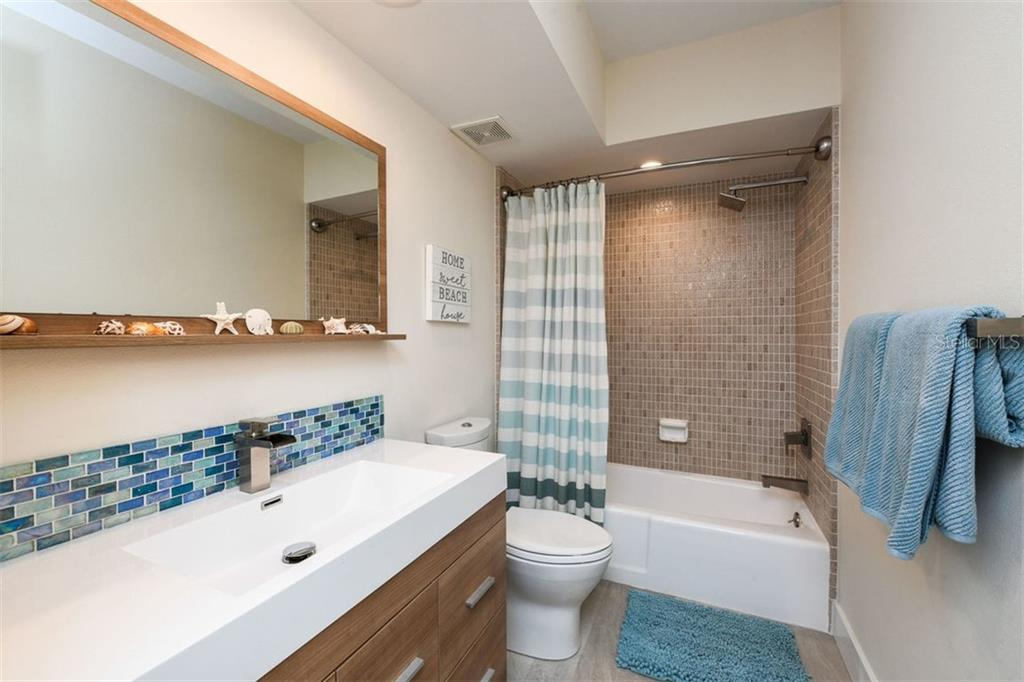 Second bathroom with shower/tub combo.  Both bathrooms feature brushed nickel finishes and waterfall faucets. - Condo for sale at 225 Hourglass Way #208, Sarasota, FL 34242 - MLS Number is A4425323