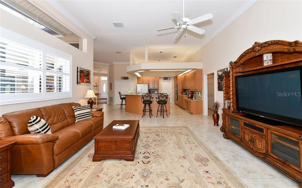 The family room looking back towards the kitchen - Single Family Home for sale at 7867 Estancia Way, Sarasota, FL 34238 - MLS Number is A4426528