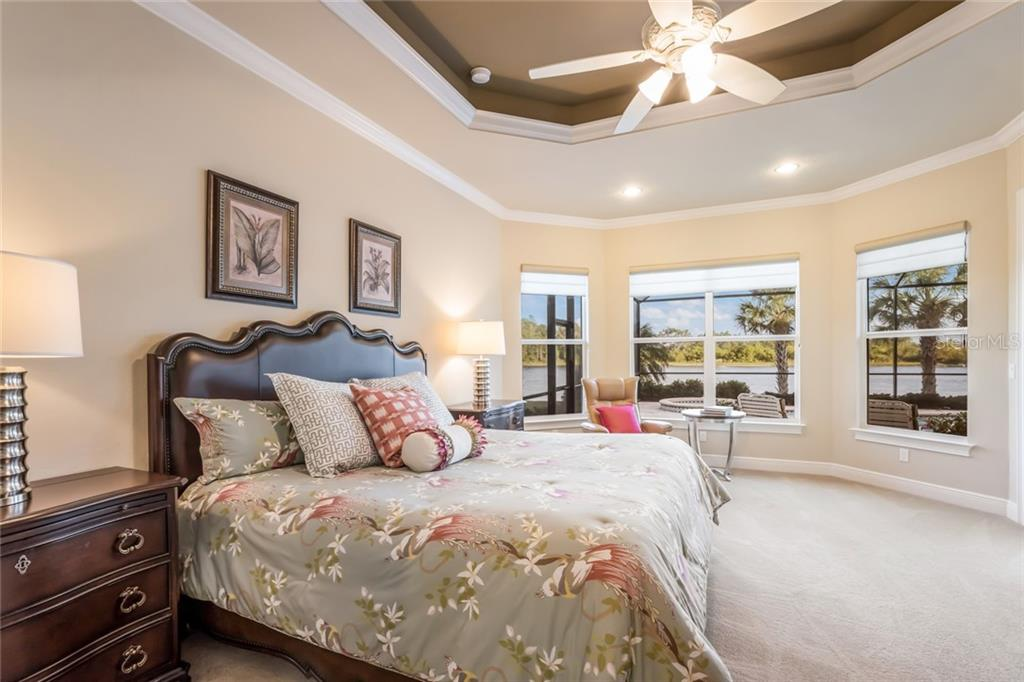 Master bedroom with tremendous lake views and double tray ceilings. - Single Family Home for sale at 19432 Newlane Pl, Bradenton, FL 34202 - MLS Number is A4432094