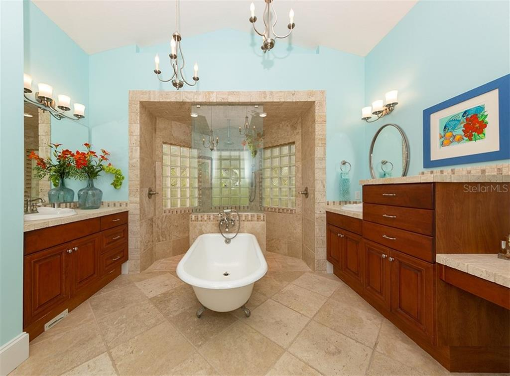 Master bath - Dual vanities with Cherry stained maple wood doors & drawers, antiqued chiseled traventine tile, custom lighting, claw tub and dual entry shower - Single Family Home for sale at 1361 Bayshore Dr, Englewood, FL 34223 - MLS Number is A4433943