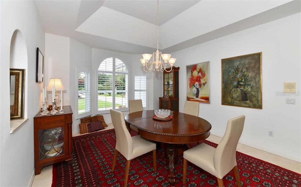 formal dining room with bay window, volume ceilings - Single Family Home for sale at 5401 Downham Meadows, Sarasota, FL 34235 - MLS Number is A4436577