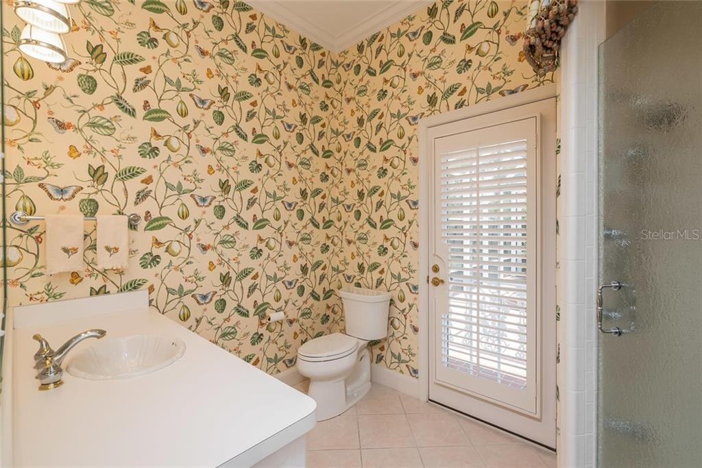 Full Pool Bath located right off the Family Room with a glass paneled French door with white plantation shutters leading to the covered pool lanai. - Single Family Home for sale at 3702 Beneva Oaks Blvd, Sarasota, FL 34238 - MLS Number is A4438878