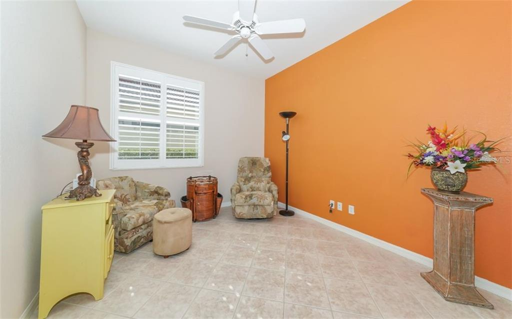 Den with tiled flooring and plantation shutters. - Single Family Home for sale at 114 Padova Way #52, North Venice, FL 34275 - MLS Number is A4442496