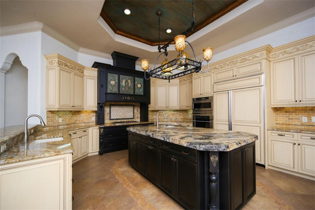 Custom cabinetry, wood paneled refrigerator, granite countertops and breakfast bar - Single Family Home for sale at 15212 Linn Park Ter, Lakewood Ranch, FL 34202 - MLS Number is A4450793