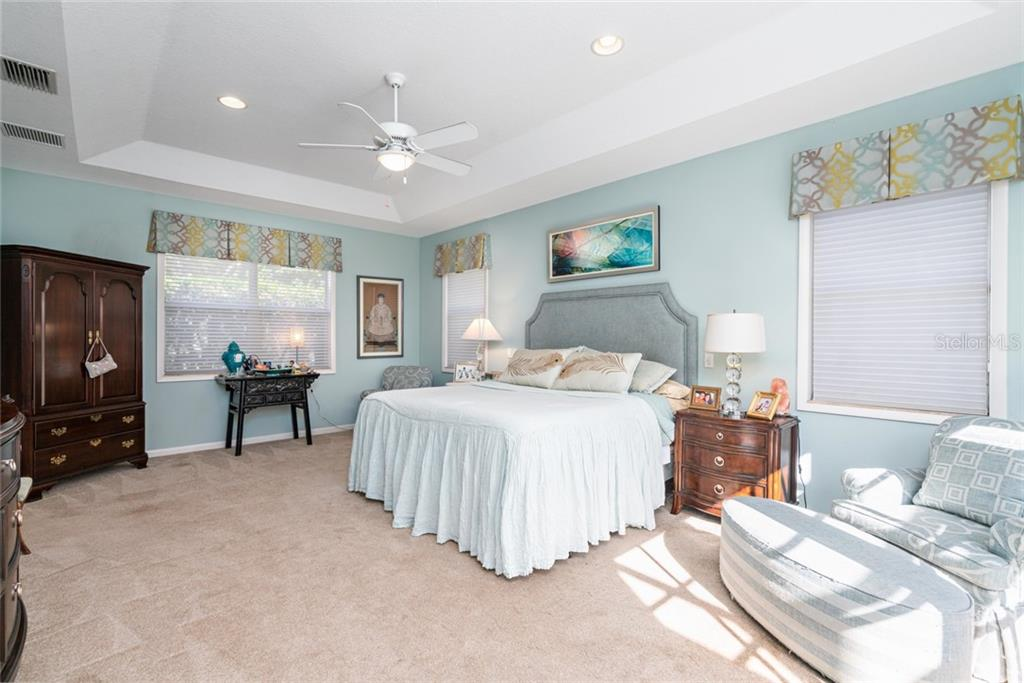 Master bedroom with french doors and tray ceiling. - Single Family Home for sale at 4557 Camino Real, Sarasota, FL 34231 - MLS Number is A4457740