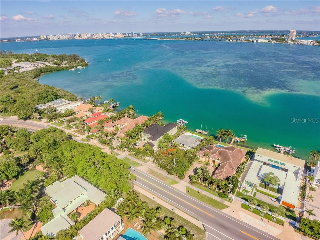 Middle house/dark roof with boat on lift, view towards downtown, Ringling Bridge , Plymouth Harbor directly across bay, Sarasota Yacht Club next to Plymouth Harbor - Single Family Home for sale at 1418 John Ringling Pkwy, Sarasota, FL 34236 - MLS Number is A4467093