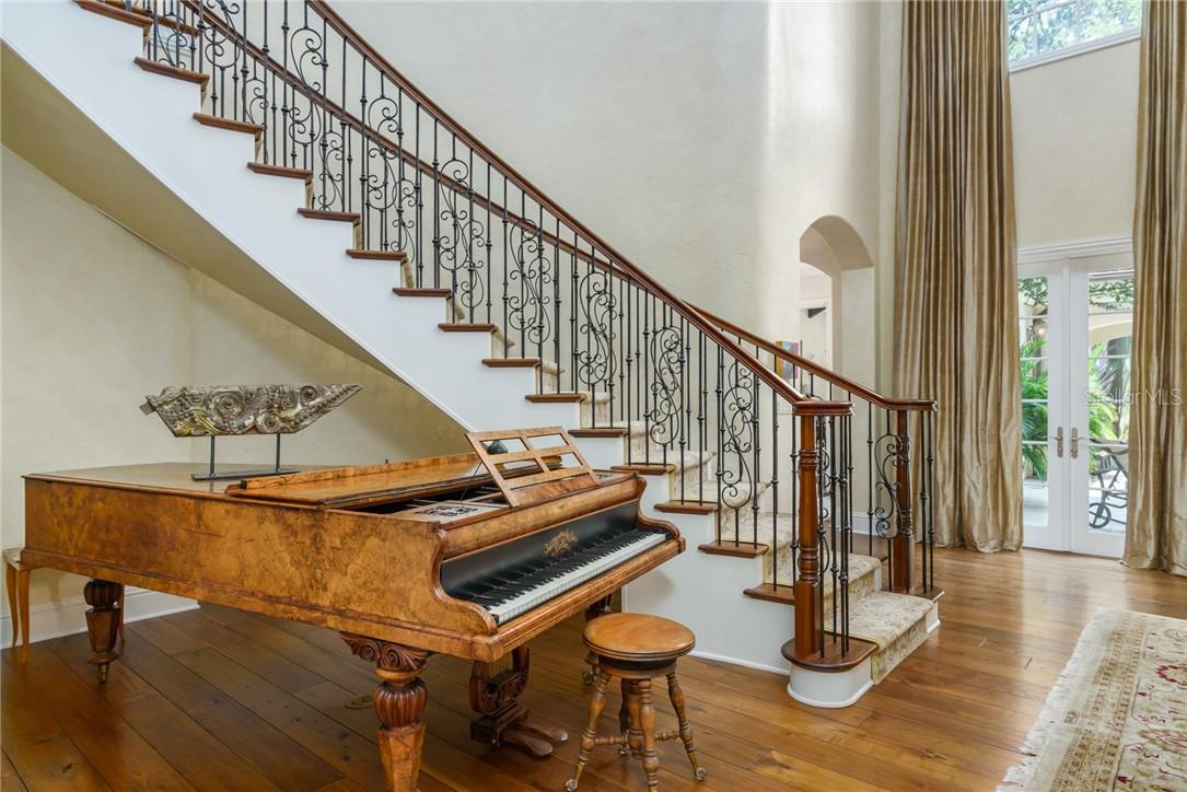 The winding staircase of wrought iron balusters and wood handrail graces one side of the living room. - Single Family Home for sale at 1807 Oleander St, Sarasota, FL 34239 - MLS Number is A4475067