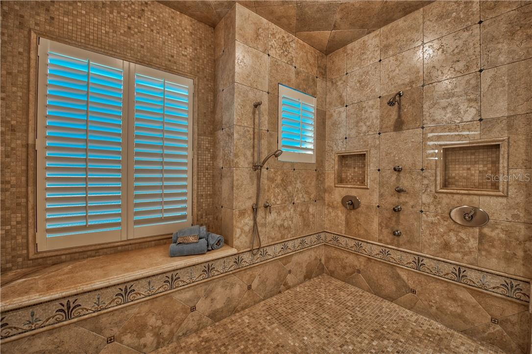 Walk-In Shower with Tile Detailing, Bench and Multiple Shower Heads - Single Family Home for sale at 8499 Lindrick Ln, Bradenton, FL 34202 - MLS Number is A4475594