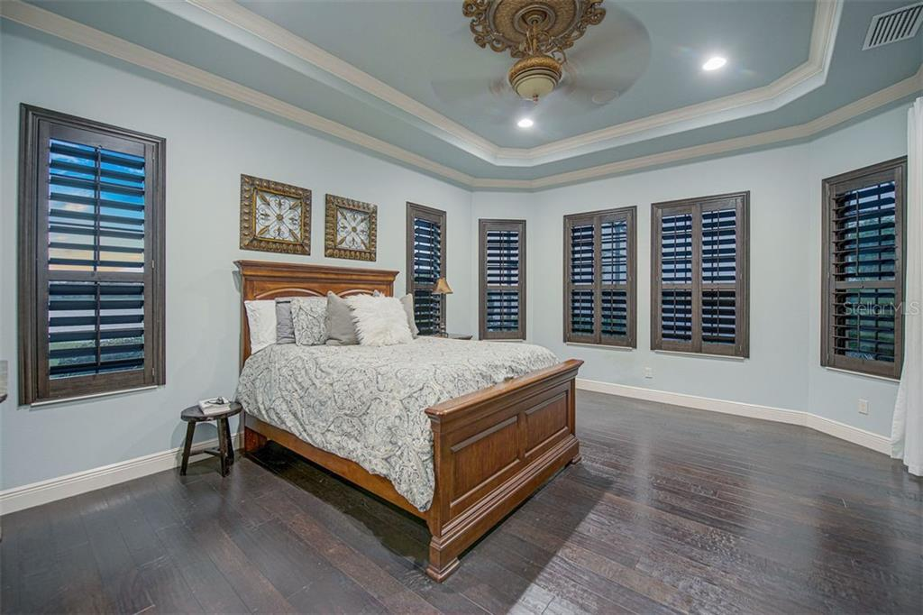 Master bedroom with plantation shutters, wood floors, and tray ceiling - Single Family Home for sale at 14507 Leopard Crk, Lakewood Ranch, FL 34202 - MLS Number is A4478709
