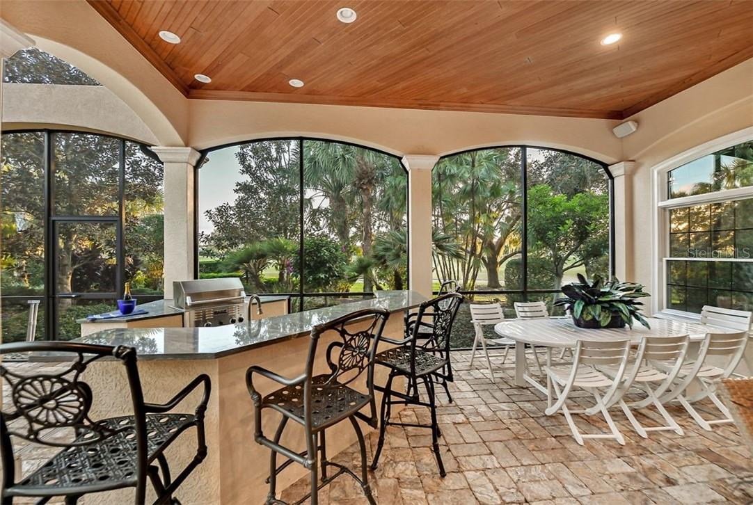 OUTDOOR KITCHEN WITH A BIG BAR FOR SEATING, WHILE VIEWING THE GOLFERS COMING IN ... - Single Family Home for sale at 8263 Archers Ct, Sarasota, FL 34240 - MLS Number is A4483993
