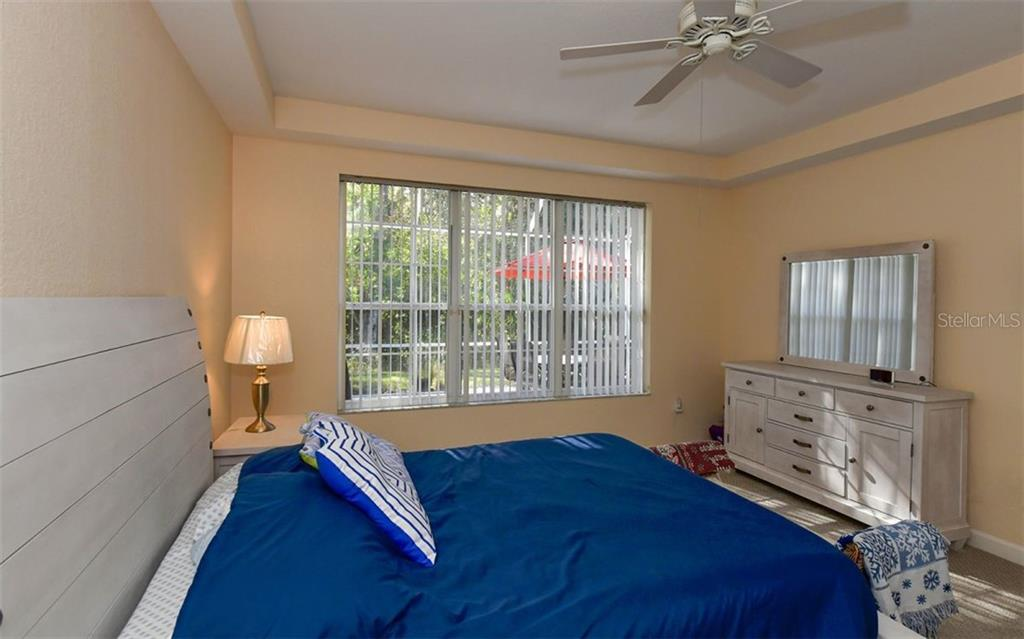 Master bedroom looks out to the lanai. - Villa for sale at 4812 Lakescene Pl, Sarasota, FL 34243 - MLS Number is A4486070