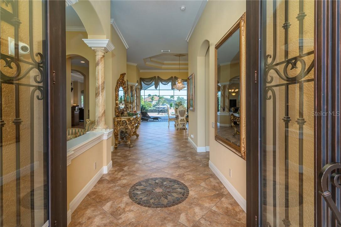 Through the tall iron front doors you will find yourself in the entry Foyer with a Dining Room to the Left and a Private Office off of a hall to the Right. - Single Family Home for sale at 11720 Rive Isle Run, Parrish, FL 34219 - MLS Number is A4486302