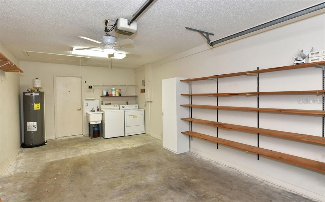 Oversized 1 car garage with laundry and storage shelves. - Villa for sale at 3314 Vivienda Blvd, Bradenton, FL 34207 - MLS Number is A4488348