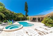 The heated salt water pool and spa invite you to sit and relax awhile... - Single Family Home for sale at 413 Bay Palms Dr, Holmes Beach, FL 34217 - MLS Number is A4184679