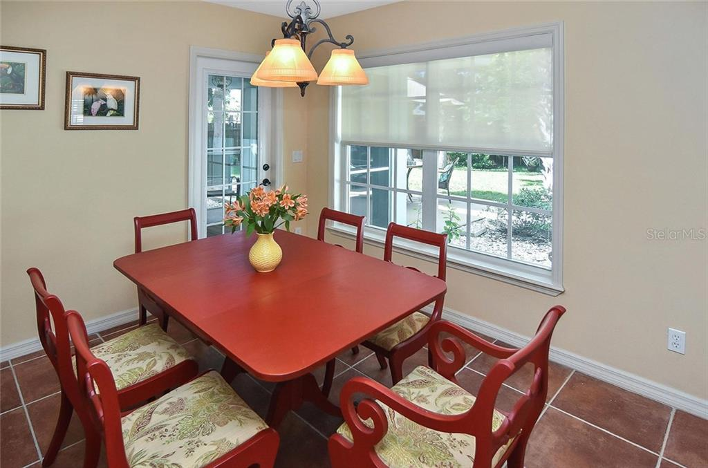 Dining room overlooking the backyard with beautiful light and airy windows. - Single Family Home for sale at 316 Alba St E, Venice, FL 34285 - MLS Number is N6102095