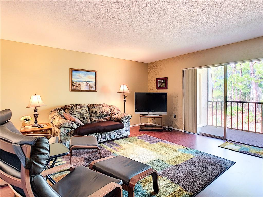 Living room with sliders to lanai - Condo for sale at 211 Rubens Dr #h, Nokomis, FL 34275 - MLS Number is N6103629