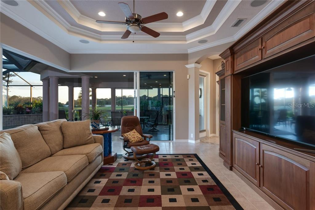 Family room with dramatic zero return sliding glass doors that open at the corner to an unobstructed view and access to the outdoors - Single Family Home for sale at 821 Adonis Pl, Venice, FL 34292 - MLS Number is N6104303