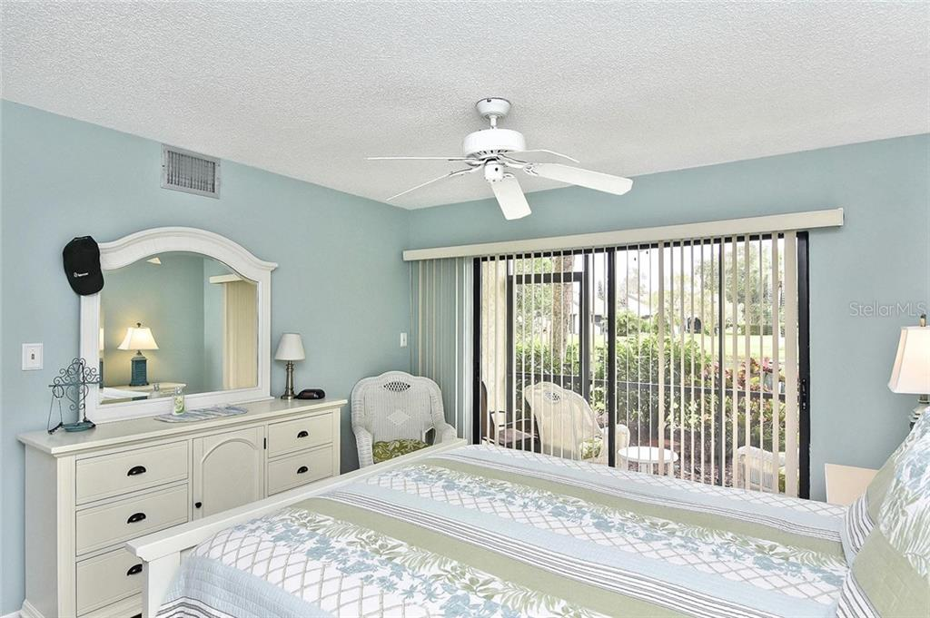 Master bedroom with sliders to lanai - Condo for sale at 626 Bird Bay Dr S #104, Venice, FL 34285 - MLS Number is N6107935