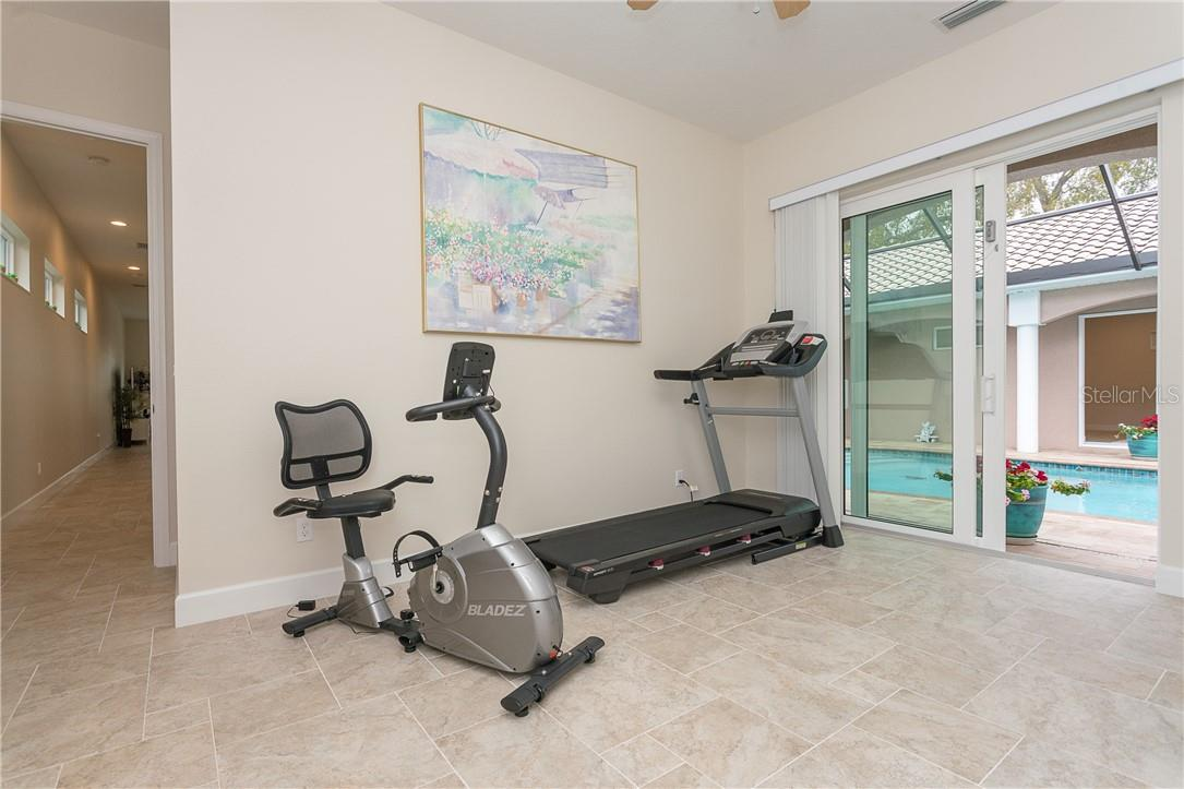 Guest room currently used as home gym, note the gorgeous porcelain tile throughout the home. - Single Family Home for sale at 1670 Maria St, Englewood, FL 34223 - MLS Number is N6113779