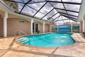 The pool features fountains along both sides. - Single Family Home for sale at 1670 Maria St, Englewood, FL 34223 - MLS Number is N6113779