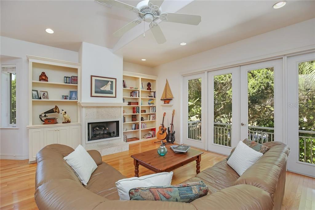 Family Room with cozy White Coral Fireplace.  Located in the Front of the Home with French Doors to Balcony overlooking Front Yard. - Single Family Home for sale at 722 Siesta Dr, Sarasota, FL 34242 - MLS Number is A4169257