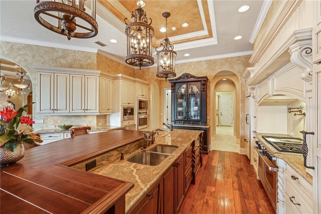 The kitchen is a masterclass of culinary design, with its gleaming suite of appliances (gas cooking), an expansive preparation island, bar seating, and more.  Beyond is a fantastic butler's pantry with floor to ceiling display cabinetry. - Single Family Home for sale at 7320 Barclay Ct, University Park, FL 34201 - MLS Number is A4200908