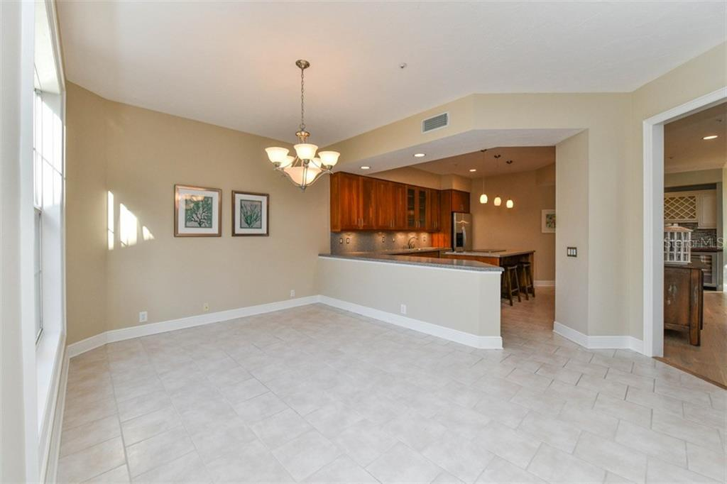 Area off the kitchen is ideal space for dining or sitting room.  Note the beautiful brick/offset tile flooring and adjacent kitchen peninsula. - Single Family Home for sale at 3947 Somerset Dr, Sarasota, FL 34242 - MLS Number is A4201541
