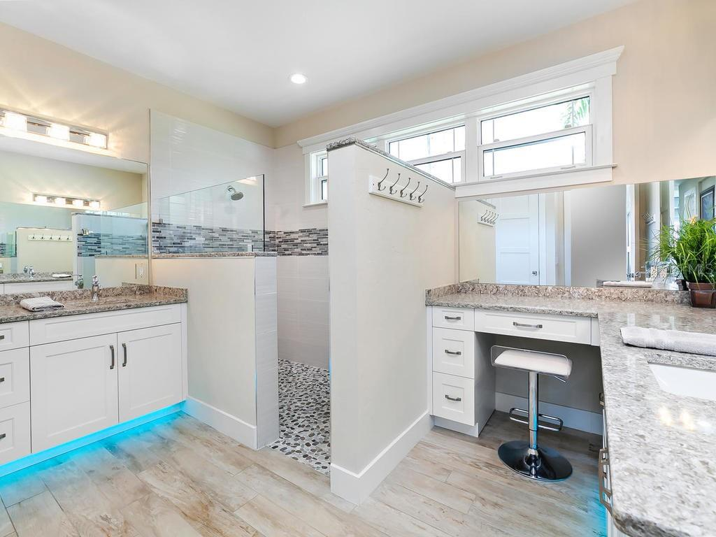 Master bath with wood cabinets, solid surface counters, dual sinks, tiled shower, vanity and under counter lighting with color changing feature - Single Family Home for sale at 7643 Cove Ter, Sarasota, FL 34231 - MLS Number is A4403215