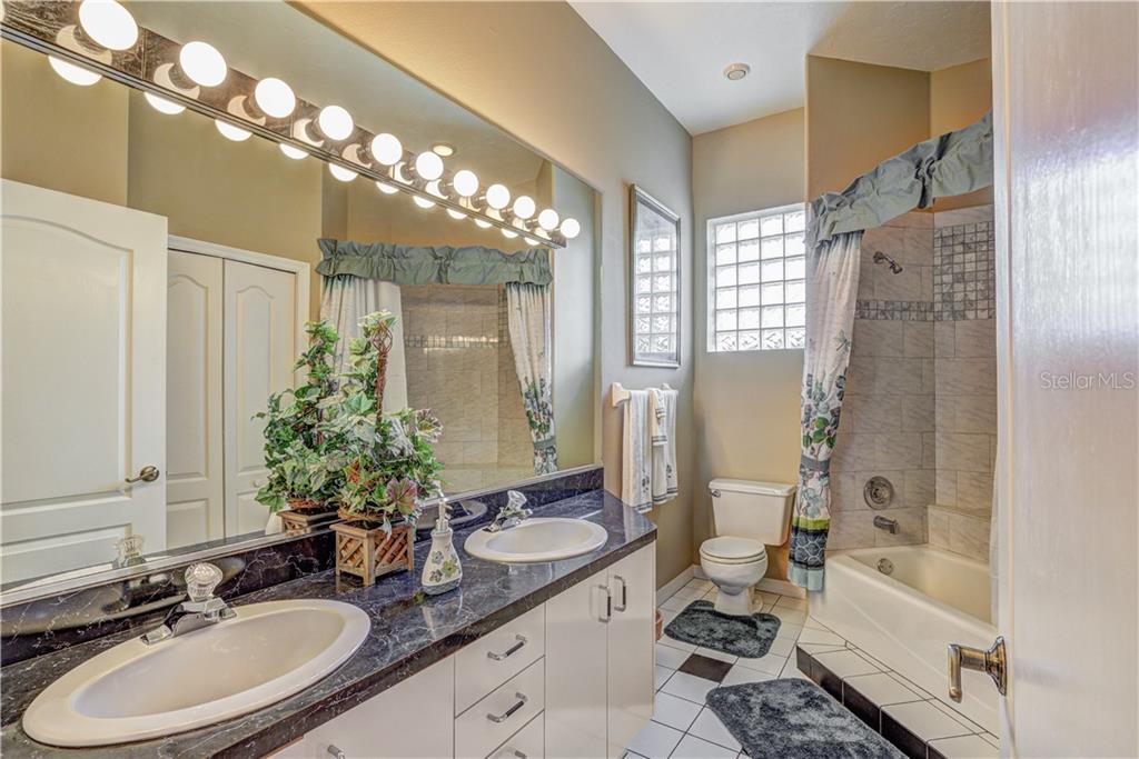 Third full bath with raised tub/shower and dual sinks, and large double door storage closet - Single Family Home for sale at 6321 W Glen Abbey Ln E, Bradenton, FL 34202 - MLS Number is A4429610