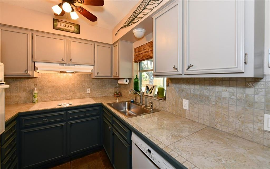 Kitchen with tile countertops. - Single Family Home for sale at 120 23rd Street Ct Ne, Bradenton, FL 34208 - MLS Number is A4438232
