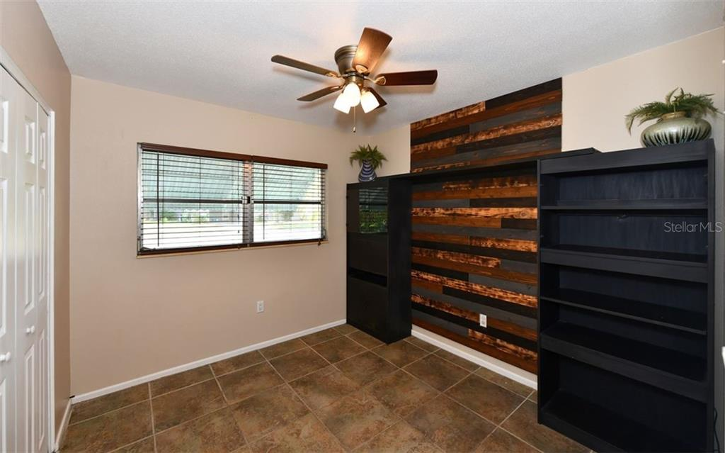 Bedroom 3 with cedar plank wall design and shelving. - Single Family Home for sale at 120 23rd Street Ct Ne, Bradenton, FL 34208 - MLS Number is A4438232