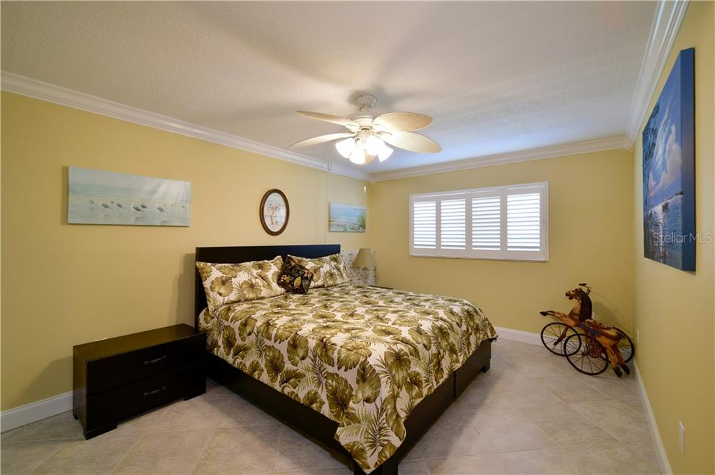 Spacious second bedroom complete with tile flooring on diagonal, plantation shutters, smooth tectured ceilings, crown, 5