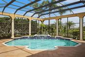 Pool and Spa.  Structured pool cage; pavers and you must see the rest of this enormous lanai.  It has a gas fireplace; built-in BBQ grill, sink and refrigeration.  A full Summer Kitchen! - Single Family Home for sale at 8365 Catamaran Cir, Lakewood Ranch, FL 34202 - MLS Number is A4187448