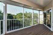 Balcony off the master bedroom with tranquil views of the fountained pond and gardens. - Single Family Home for sale at 3947 Somerset Dr, Sarasota, FL 34242 - MLS Number is A4201541