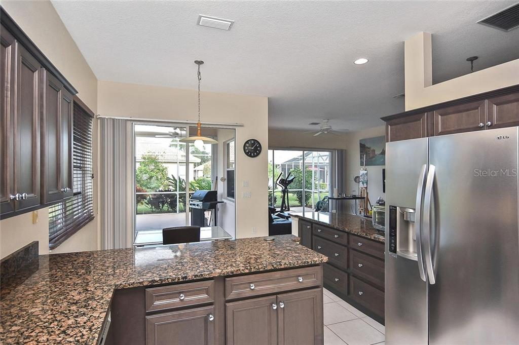 Kitchen to dinette and great room - Single Family Home for sale at 724 Silk Oak Dr, Venice, FL 34293 - MLS Number is N6102801