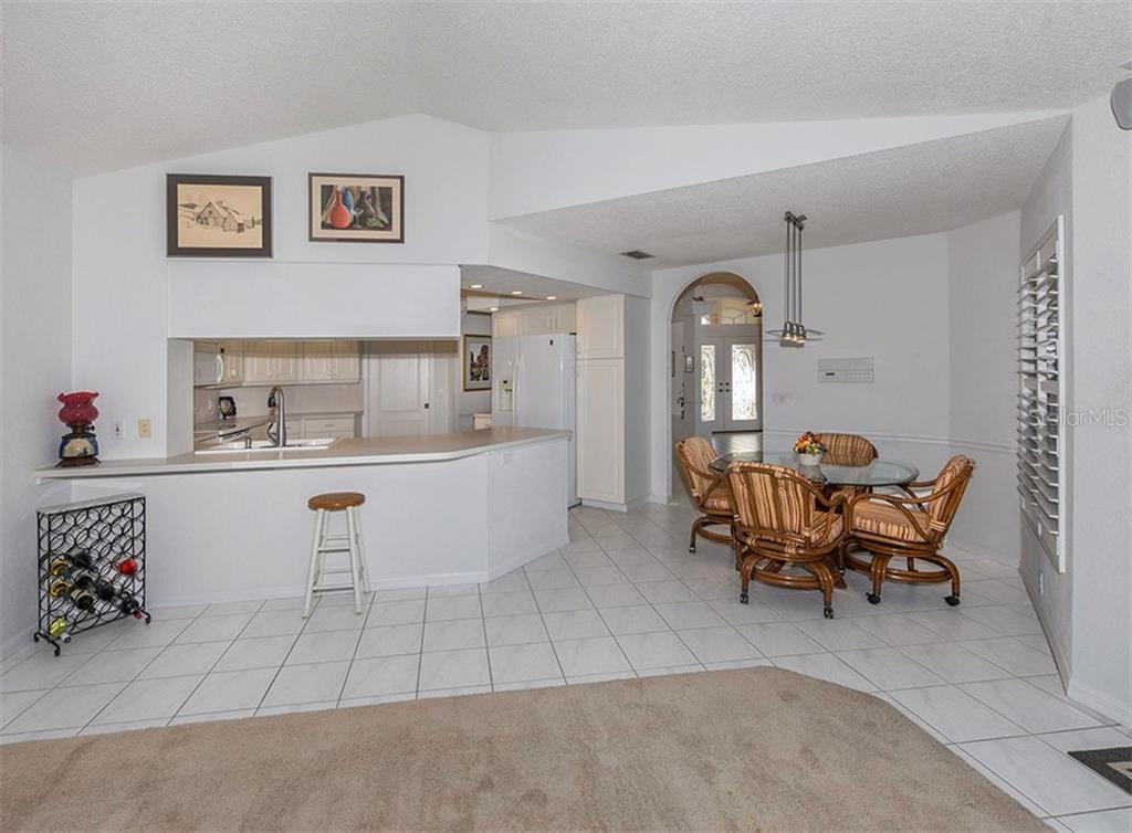Breakfast bar, kitchen, dinette from family room - Single Family Home for sale at 515 Park Estates Sq, Venice, FL 34293 - MLS Number is N6103193